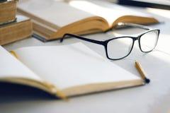 De heldere zon verlicht oude encyclopedieën, een notitieboekje, een eenvoudig potlood en glazen stock afbeelding