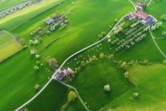 De heldergroene gebieden met landbouwbedrijven van een vogel` s oog bekijken op een de lenteochtend stock foto's