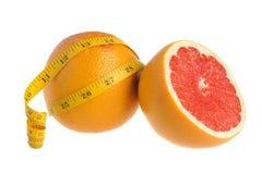 De helft en een gehele die grapefruit met maatregelenband wordt verpakt op wit Stock Foto