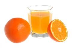 De helft en een gehele die sinaasappel met een glas met citrusvruchtensap wordt gevuld Royalty-vrije Stock Afbeeldingen