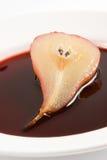 De helft van de peer stroopte in rode wijn Stock Fotografie