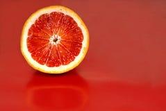 De helft van een bloedsinaasappel op een rode achtergrond Stock Fotografie
