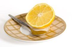 De helft van een citroen met een theelepeltje stock fotografie
