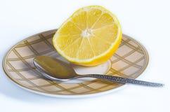 De helft van een citroen met een theelepeltje royalty-vrije stock afbeeldingen