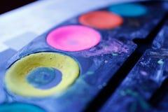 De helft van een waterverfpalet met gele, roze, rode en groene verf Sluit omhoog geschoten stock afbeelding