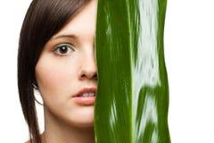 De helft van het gezicht van de vrouw met groen blad Stock Foto's