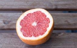 De helft van rode grapefruit op een houten lijst Royalty-vrije Stock Afbeeldingen