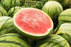 De helft van rode kuiltjes gemaakte in watermeloen, close-up stock afbeeldingen