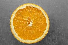 De helft van sinaasappel met ongelijke plakken Stock Foto's