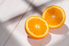 De helft van sinaasappel op witte houten lijst Royalty-vrije Stock Foto's