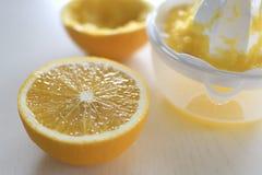 De helft van verse sinaasappel, naast juicer Royalty-vrije Stock Afbeeldingen