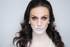 De helft van vrouwelijk gezicht is in de schaduw gesteld met beige stichtingsvrouw omhoog maakt royalty-vrije stock afbeeldingen