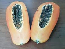 de helften van het papajafruit met zaden op houten lijst, achtergrond en textuur royalty-vrije stock afbeeldingen