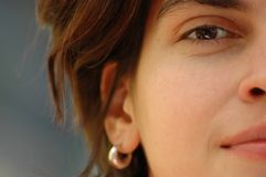 De helftgezicht van het meisje met oorring. Stock Foto's