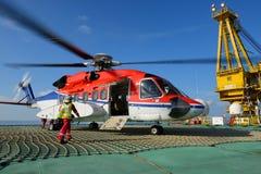 De helikopter landende ambtenaar gaat naar helikopter bij booreiland royalty-vrije stock afbeelding