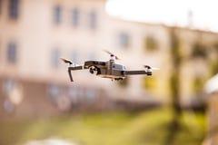 De helikopter van de hommelvierling met hoge resolutie het digitale camera vliegen die in de blauwe hemel over de stad hangen Royalty-vrije Stock Foto