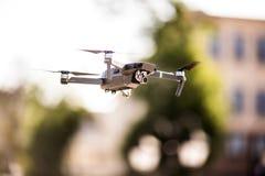 De helikopter van de hommelvierling met hoge resolutie het digitale camera vliegen die in de blauwe hemel over de stad hangen Stock Fotografie