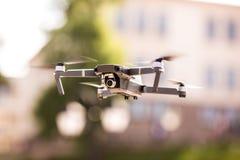 De helikopter van de hommelvierling met hoge resolutie het digitale camera vliegen die in de blauwe hemel over de stad hangen Royalty-vrije Stock Afbeeldingen
