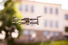 De helikopter van de hommelvierling met hoge resolutie het digitale camera vliegen die in de blauwe hemel over de stad hangen Stock Foto's