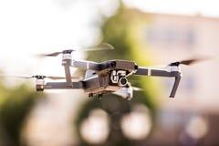 De helikopter van de hommelvierling met hoge resolutie het digitale camera vliegen die in de blauwe hemel over de stad hangen Royalty-vrije Stock Fotografie