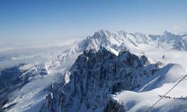De helling van de sneeuw met berg-skiërs Stock Foto's