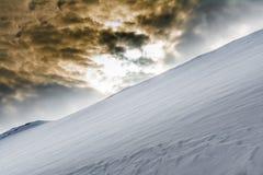 De helling van sneeuwberg en donkere brutale hemel sluit plaatsend s Stock Fotografie