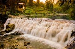 De helling van waterval en zonsondergang Stock Foto's
