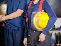 De Helmen van de brandbestrijdersholding bij Brandweerkazerne Royalty-vrije Stock Afbeeldingen
