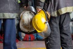 De Helmen van de brandweerliedenholding bij Brandweerkazerne Stock Foto's