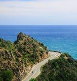 De hemel blauwe oceaan van weg groene bergen Stock Afbeelding