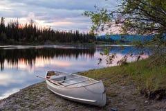 De hemel en de kano van de zonsondergang bij Teslin Rivier Yukon Canada Royalty-vrije Stock Afbeeldingen