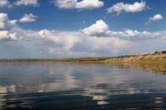 De hemel in het water, verlaten strandmeer, de zomerhemel, aard, blauwe wolk wordt weerspiegeld die, Stock Afbeeldingen