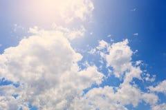 De hemel met witte wolken en verlichting van de Zon stock foto