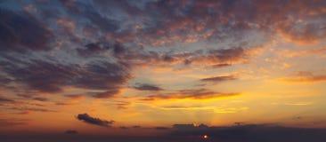 De hemel tijdens een kleurrijke, heldere oranje zonsondergang, de stralen van de zon maakt hun manier door de wolken stock afbeeldingen