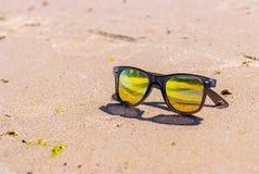 De hemel wordt weerspiegeld in zonnebril, strand stock fotografie