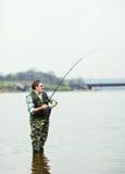 De hengelsport van de visser op de rivier stock afbeeldingen