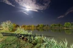 De hengelsportstaven van de karper spinnende spoel bij peul de status Nacht die, Karperstaven, Cloudscape-Volle maan over meer vi Royalty-vrije Stock Foto