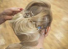 De herenkapper maakt de bruid tot een huwelijkskapsel met de toebehoren van het haardetail, close-up achtermening stock foto's
