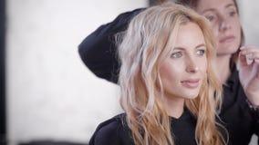 De herenkappervrouw verbetert sloten op hoofd van volwassen blondecliënt die van herenkapper, stijl maken stock videobeelden