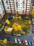 De herfst Ñ  ityscape van de binnenplaats met kinderen` s speelplaats en geparkeerde auto's royalty-vrije stock afbeeldingen