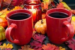 De herfst die met kleine pompoenen en een rode kaarshouder plaatsen die licht op twee koppen van ochtendkoffie uitzenden stock fotografie