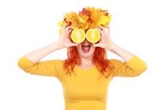 De herfst grappige vrouw met gele bladeren op haar hoofd en sinaasappelen royalty-vrije stock afbeelding