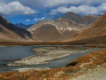 De herfst in het hooggebergte van de vallei: de rivierstromen aan de voorgrond met een blauwe oppervlakte van water onder de bank Stock Afbeeldingen
