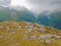 De herfst in hoge Alpiene bergen De donkere pieken raken zware nevelige wolken Koud en vochtig eind van de dag in Alpen Royalty-vrije Stock Afbeelding