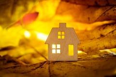 De herfst houten stuk speelgoed huis met gele bladeren Royalty-vrije Stock Foto