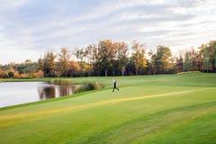 De herfst, meer, golfcursus Jong volwassen meisje die op green lopen Royalty-vrije Stock Afbeeldingen