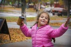 In de herfst, op de straat, drinkt een klein meisje cacao, is zij royalty-vrije stock afbeeldingen