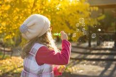 De herfst openluchtportret van de blazende zeepbels van een kindmeisje stock fotografie