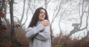 De herfst vibes, comfortabele atmosfeer Het charmeren van donkerbruine vrouw met lang donker haar omhelst zich die zich in de her stock video