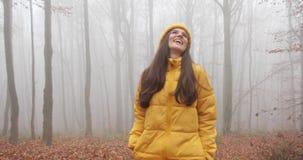 De herfst vibes, draagt de mistige bos Aantrekkelijke donkerbruine vrouw met lang haar gele uitrusting en loopt over het bos stock footage